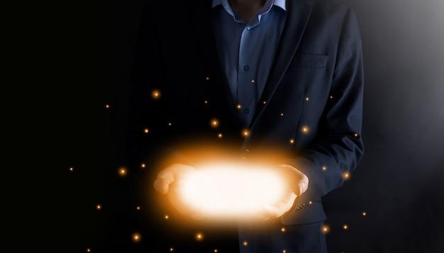 Biznes człowiek trzymając się za ręce otwarte ze świecącymi światłami na ciemnym tle.