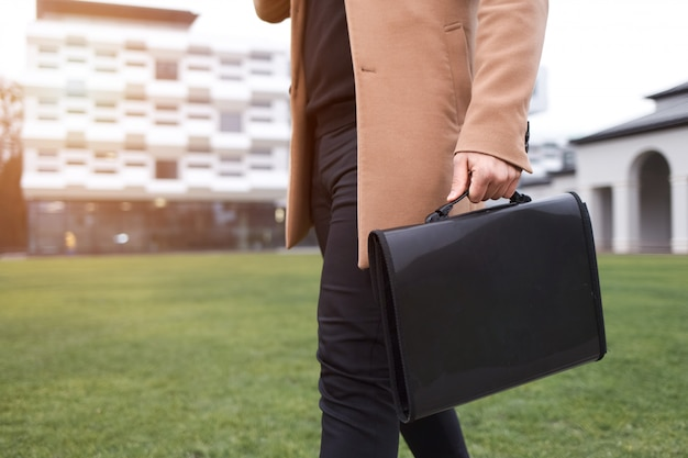 Biznes człowiek w brązowym płaszczu i torbie z dokumentami w ręku idzie na wor