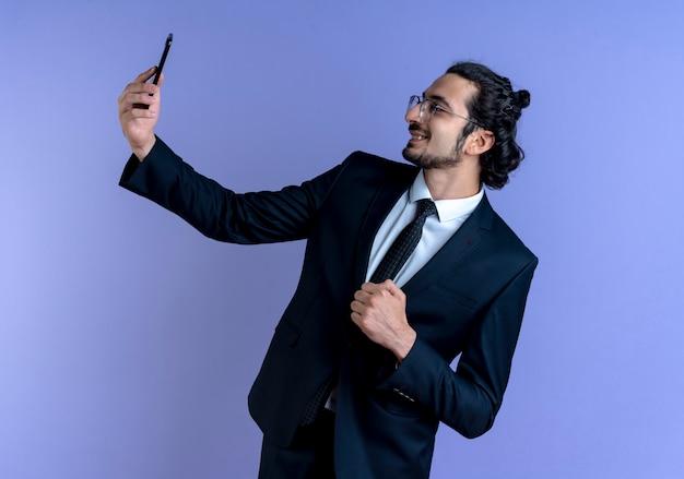 Biznes człowiek w czarnym garniturze i okularach, biorąc selfie za pomocą swojego smartfona zaciskając pięść, uśmiechając się z radosną twarzą stojącą nad niebieską ścianą