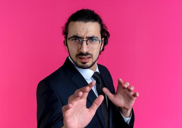 Biznes człowiek w czarnym garniturze i okularach czyniąc gest obrony rękami z niesmakiem stojąc na różowej ścianie