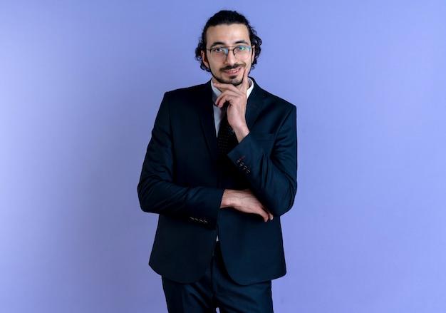 Biznes człowiek w czarnym garniturze i okularach patrząc do przodu z ręką na brodzie uśmiechnięty pewnie stojący nad niebieską ścianą