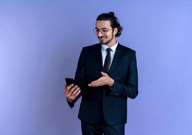 Biznes człowiek w czarnym garniturze i okularach patrząc na ekran swojego smartfona uśmiechnięty stojący nad niebieską ścianą