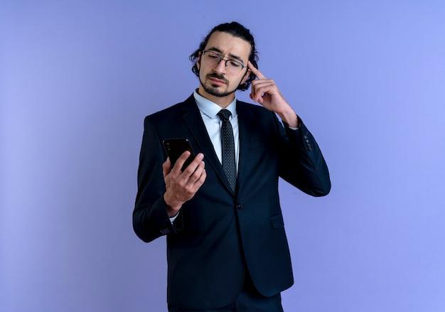 Biznes człowiek w czarnym garniturze i okularach patrząc na ekran swojego smartfona, wskazując palcem na swoją świątynię, skupiony na zadaniu stojącym nad niebieską ścianą