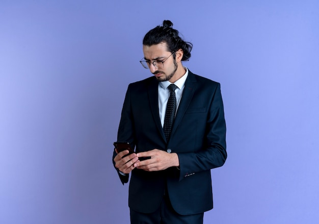 Biznes człowiek w czarnym garniturze i okularach patrząc na ekran swojego smartfona z poważną twarzą stojącą nad niebieską ścianą