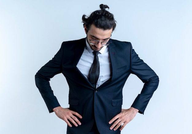 Biznes człowiek w czarnym garniturze i okularach patrząc w dół z rękami na biodrze, zmęczony i znudzony, stojąc na białej ścianie