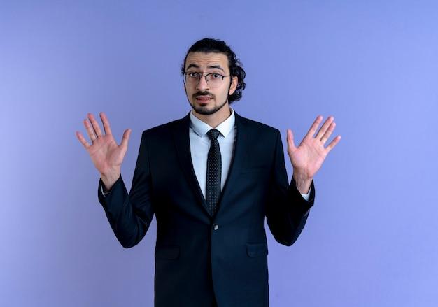 Biznes człowiek w czarnym garniturze i okularach podnosząc ręce w kapitulacji, patrząc zdezorientowany stojąc nad niebieską ścianą