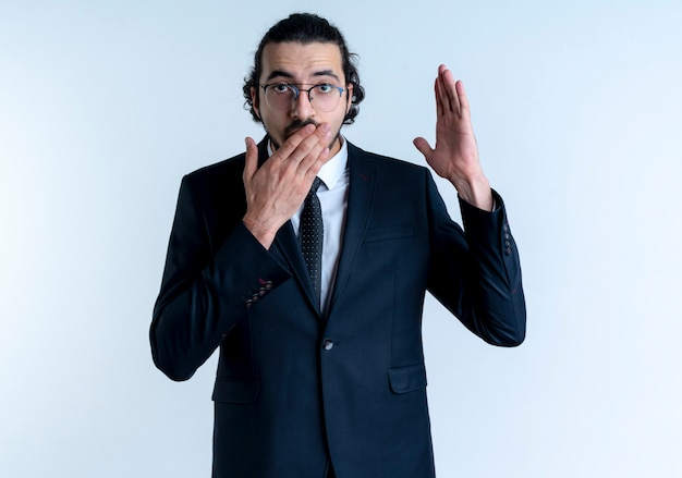 Biznes człowiek w czarnym garniturze i okularach podnosząc rękę patrząc zaskoczony, obejmując usta ręką stojącą na białej ścianie