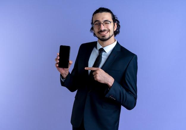 Biznes człowiek w czarnym garniturze i okularach pokazując smartfon wskazując palcem na to, uśmiechając się i mrugając stojąc na niebieskiej ścianie