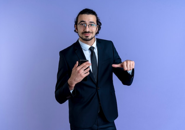 Biznes człowiek w czarnym garniturze i okularach pokazuje smartfon, wskazując palcem na to uśmiechnięty pewnie stojący nad niebieską ścianą