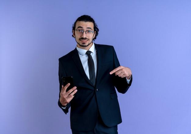 Biznes człowiek w czarnym garniturze i okularach pokazuje smartfon wskazujący palcem na to uśmiechnięty pewnie stojący nad niebieską ścianą 2