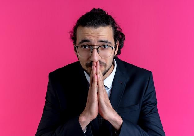 Biznes człowiek w czarnym garniturze i okularach, trzymając dłonie razem, modląc się i błagając z nadzieją, stojąc nad różową ścianą