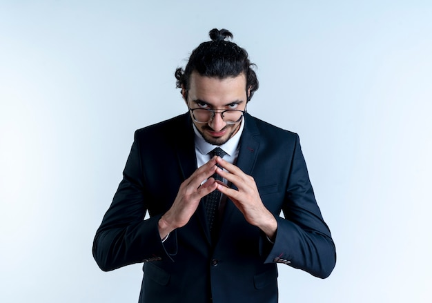 Biznes człowiek w czarnym garniturze i okularach, trzymając dłonie razem patrząc do przodu chytrze czekając na coś stojącego nad białą ścianą