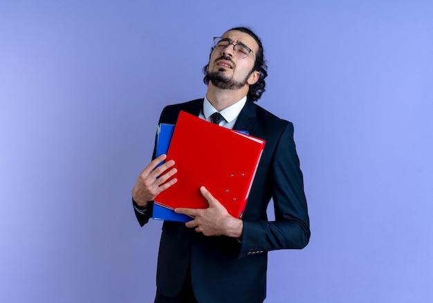 Biznes człowiek w czarnym garniturze i okularach, trzymając foldery z zamkniętymi oczami, zmęczony i znudzony stojąc nad niebieską ścianą