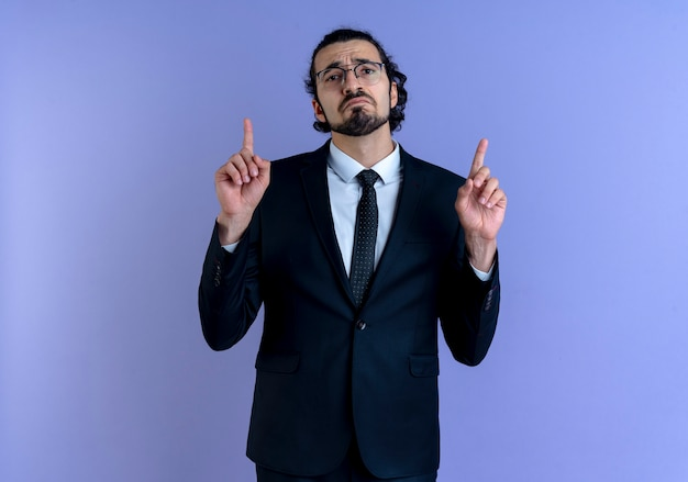 Biznes człowiek w czarnym garniturze i okularach, wskazując palcami wskazującymi, patrząc do przodu ze smutnym wyrazem stojącym nad niebieską ścianą