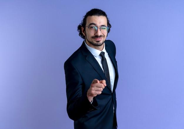 Biznes człowiek w czarnym garniturze i okularach, wskazując palcem wskazującym do przodu uśmiechnięty pewnie stojący nad niebieską ścianą