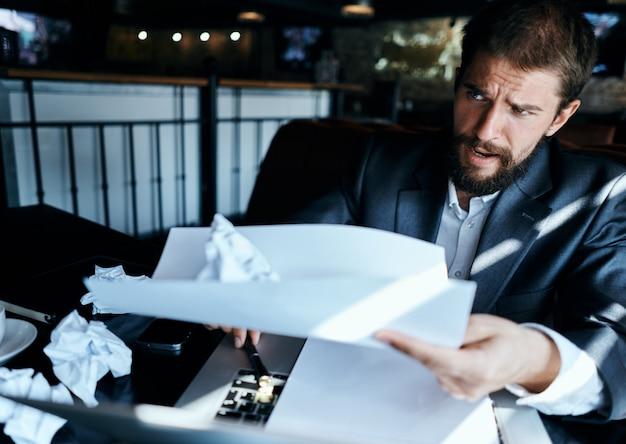 Biznes człowiek w kawiarni siedzi przy stole dokumenty laptop zmięty papier kierowniczy emocje stylu życia