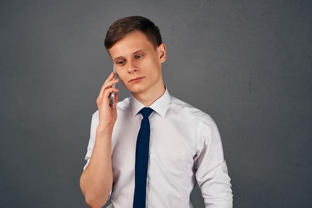 Biznes człowiek w koszuli z krawatem z telefonem w jego rękach praca komunikacji. zdjęcie wysokiej jakości