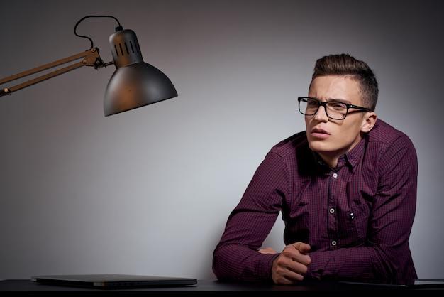 Biznes człowiek w okularach i koszuli siedzi przy stole w ciemnym pokoju z lampą
