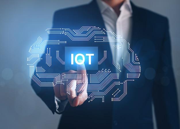 Biznes człowiek wskazując przycisk iot z abstrakcyjnymi urządzeniami chip.