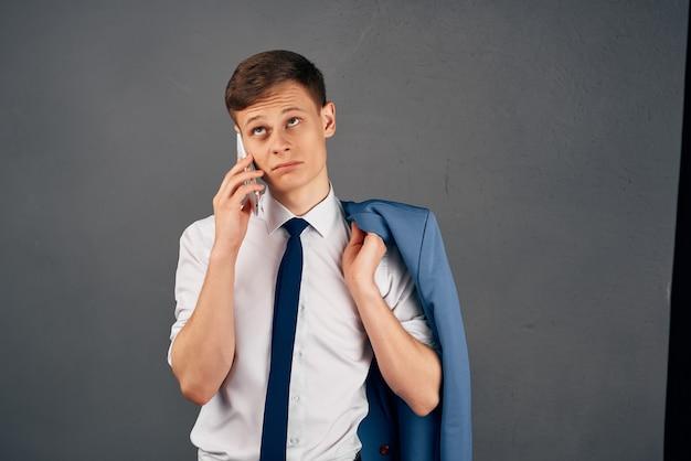 Biznes człowiek z kurtką na ramieniu rozmawia przez kierownika biura telefonu. zdjęcie wysokiej jakości