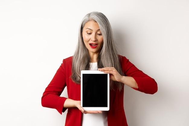 Biznes. dojrzała azjatycka pani biurowa pokazuje ekran cyfrowego tabletu i patrzy w dół zdumiony, stojąc na białym tle.