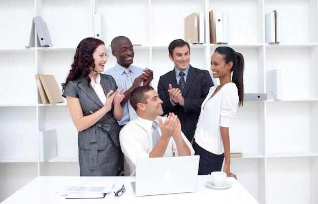 Biznes drużyna oklaskuje kolegi w biurze