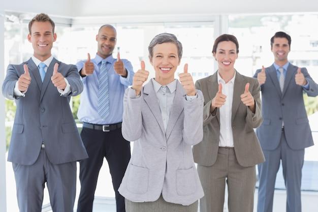 Biznes drużyna ono uśmiecha się przy kamerą pokazuje aprobaty