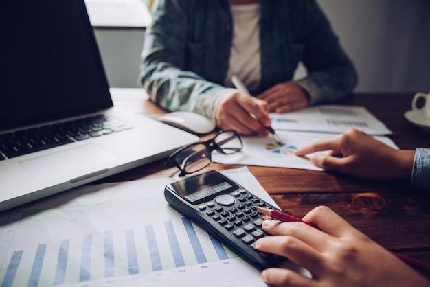 Biznes drużyna pracuje z laptopem i kalkulatorem w otwartej przestrzeni biurze. raport ze spotkania w toku