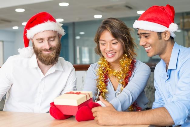 Biznes drużyna świętuje boże narodzenia przy biurem