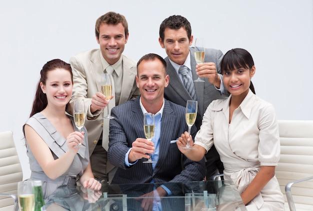 Biznes drużyna świętuje sukces z szampanem w biurze