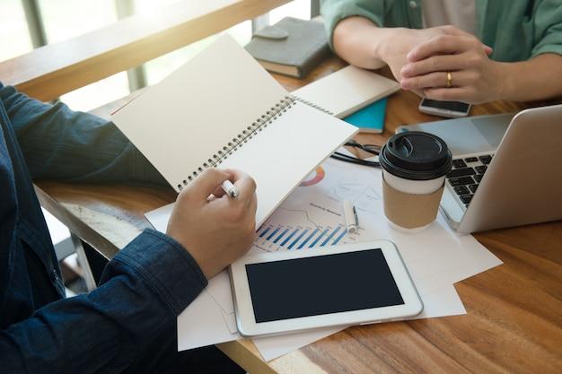 Biznes drużynowa odprawa marketingowa strategia z nutowym książki biurem domowym.