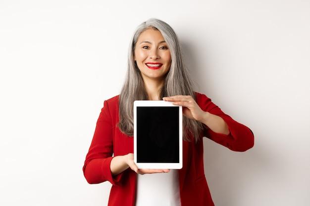 Biznes. dumny azjatycki menedżer pokazuje pusty ekran cyfrowego tabletu, uśmiechając się i demonstrując promocję, stojąc na białym tle.