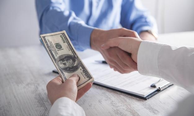 Biznes dziewczyna daje łapówkę pracownikowi w biurze. korupcja, łapówka