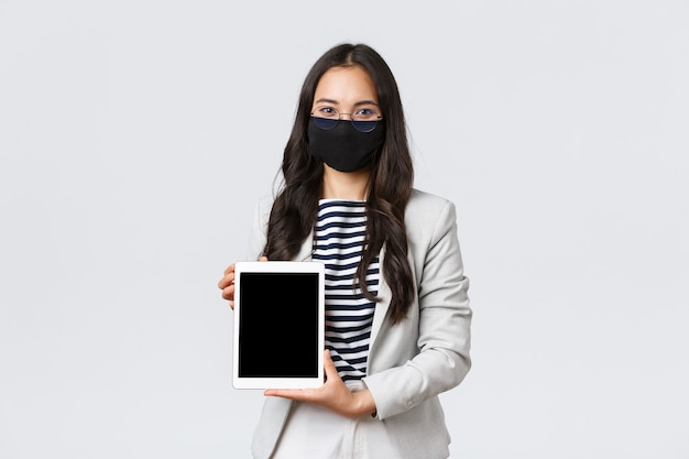 Biznes, finanse i zatrudnienie, covid-19 zapobieganie wirusowi i koncepcji dystansu społecznego. pewna siebie pośrednik w obrocie nieruchomościami pokazujący ofertę dla klienta na ekranie cyfrowego tabletu, nosząc maskę na twarz