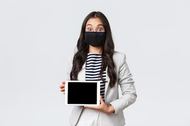 Biznes, finanse i zatrudnienie, covid-19 zapobieganie wirusowi i koncepcji dystansu społecznego. podekscytowana azjatycka bizneswoman w masce na twarz i okularach szeroko otwiera oczy, pokazując cyfrowy wyświetlacz tabletu