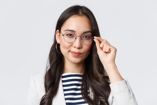 Biznes, finanse i zatrudnienie, koncepcja kobiet przedsiębiorców sukcesu. zbliżenie: pewna siebie młoda azjatycka bizneswoman naprawiająca okulary i wyglądająca na zdeterminowaną, gotową do podpisania transakcji