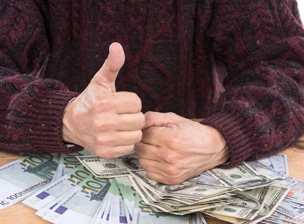 Biznes, finanse, koncepcja bankowości. zbliżenie na ręce człowieka i pieniądze w dolarach i euro