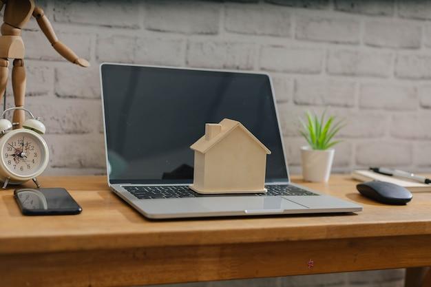 Biznes, finanse, oszczędności, drabina nieruchomości lub koncepcja kredytu hipotecznego, model domu z drewna na laptopie komputerowym