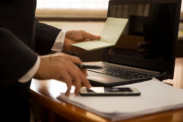 Biznes finansowy ręka trzymać oświadczenie książki i pracować z laptopem.