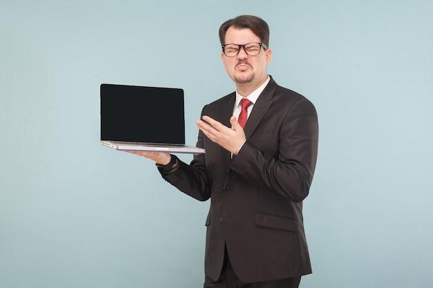 Biznes, gadżety, technologie. biznesmen posiadający zepsuty ulubiony top na kolanach, zły dzień. wewnątrz, studio strzał, na białym tle na jasnoniebieskim lub szarym tle
