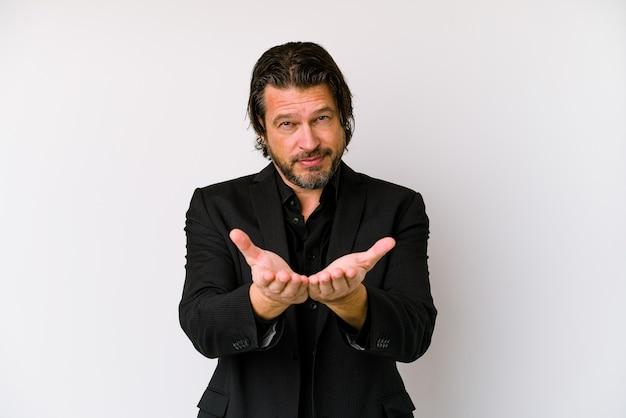 Biznes holenderski mężczyzna w średnim wieku na białym tle na białej ścianie, trzymając coś oburącz, prezentacja produktu