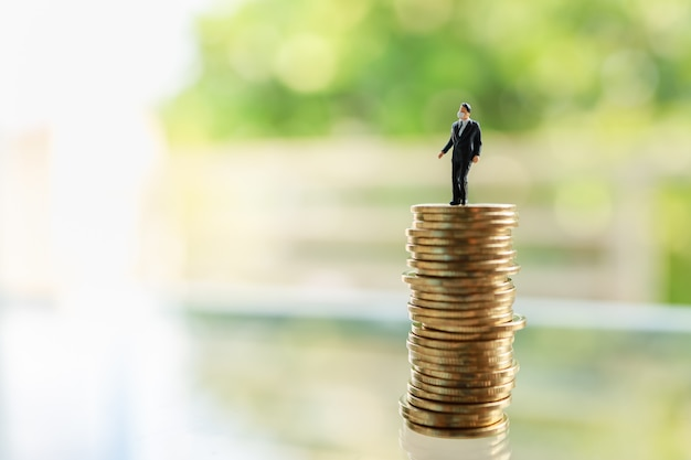 Biznes i econony cocept. biznesmen postaci miniaturowi ludzie z twarzy maski pozycją na stercie monety z zieleni i kopii przestrzenią.
