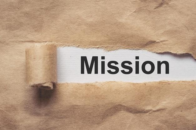 Biznes i finanse. podarty brązowy papier, tekst - misja