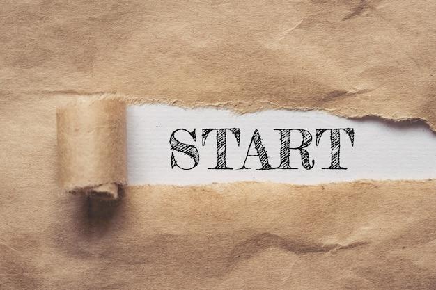 Biznes i finanse. podarty papier brązowy na białym tle, tekst - start