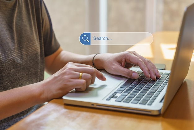 Biznes i praca z domu i koncepcja technologii. azjatycki człowiek za pomocą i wpisując komputer laptop z ikoną pola paska wyszukiwania i mobilny smartfon na drewnianym stole...