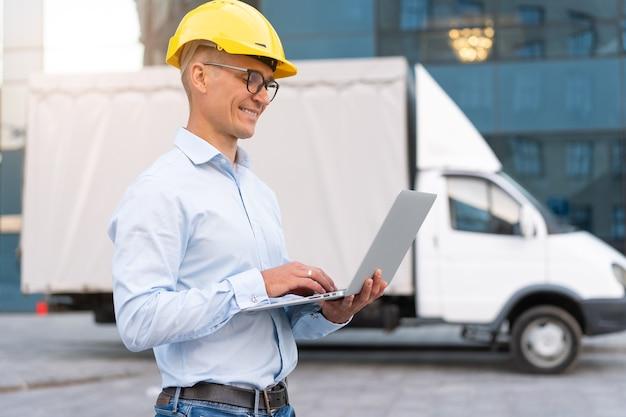 Biznes. inżynier pracownik kask ochronny używaj kontroli laptopa inspektor procesu roboczego nadzorca żółty kask okulary firma transportowa budynek biurowy i tło ciężarówki