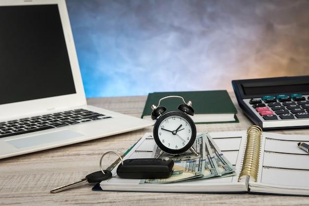 Biznes - kluczyk do samochodu, pieniądze na laptopa i notatnik na biurku.
