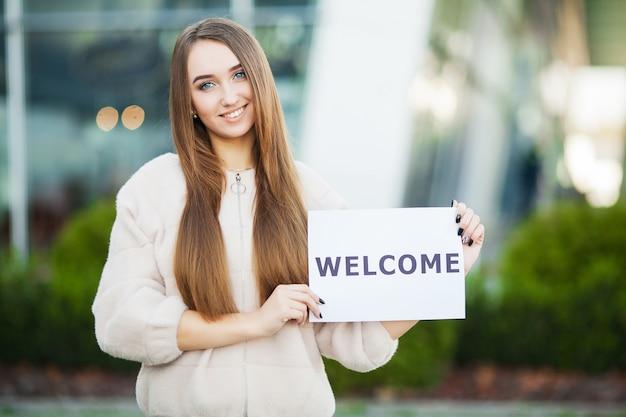 Biznes kobiet z tabliczką z wiadomością powitalną