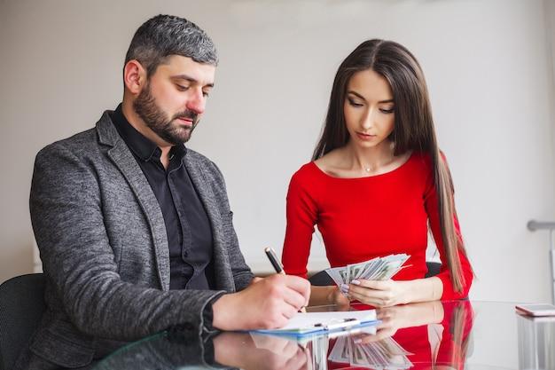 Biznes kobieta daje pieniądze dla mężczyzn.
