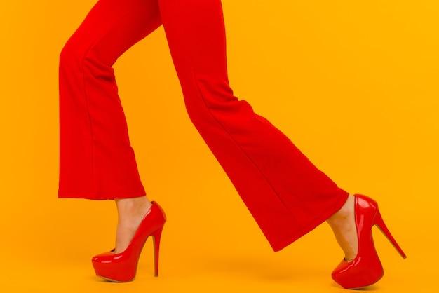 Biznes kobieta gdzieś działa śpiesząc się na białym tle na żółtym tle. stylowe czerwone szpilki i spodnie na cienkich kobiecych nogawkach
